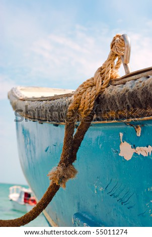 Boat on sea. Old blue painted fishing boat tied with rope at seacoast