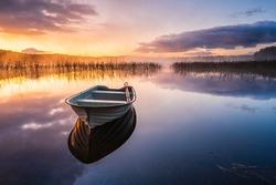 Boat on still lake at sunrise, Sweden.