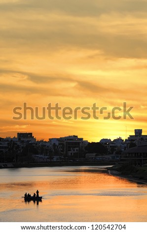 Boat on sunset river and silhouettes of the evening city - stock photo