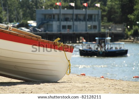 BOAT ON THE BEACH. A small row boat sits idle on the beach while a small passenger ferry boat passes by in the back ground.