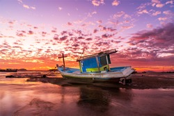 Boat on the beach at sunset time. Seascape, Fisherman boat  in tropical beach with beautiful sunset time. Traditional fishing boat long tail at the beach during sunrise. Rawai beach,Phuket, Thailand.
