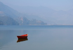Boat on the lake, fishing boat in a calm lake water,old wooden fishing boat,wooden fishing boat in a still lake water.