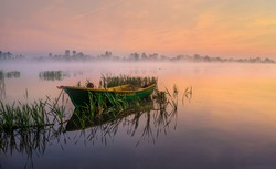 Boat on the lake in the rays of the rising sun and fog, zemborzycki lake