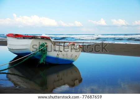 Boat on the shore against sea waves