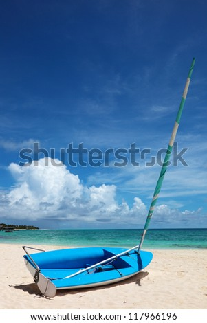 Boat on the shore of the lagoon on the background of the rainbow. Maldives, Rasdhoo Atoll, Kuramathi Island