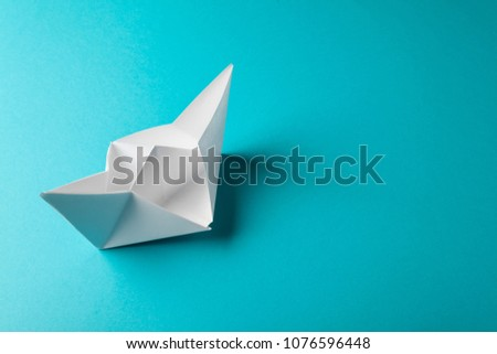 boat paper origami on the blue background. studio shot