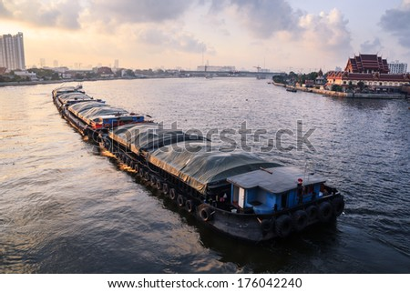 Boat pulled by a tugboat cargo carry the product of morning time at Thailand