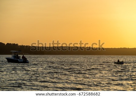 Boat pulling a toob at sunset on a Texas lake