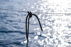 Boat railing detail. Black rope tied knot on stainless steel wire cable guard rail, bokeh sea water surface. Sailing travel at Aegean sea, Greece. Summer vacations advertise template, Space,