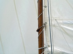 Boat sail and mast; good copy space over white sail