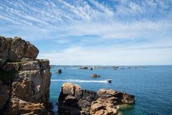 Boat sailing between rocks at Pink Granite Coast, Plougrescant, Cotes-d'Armor, France.