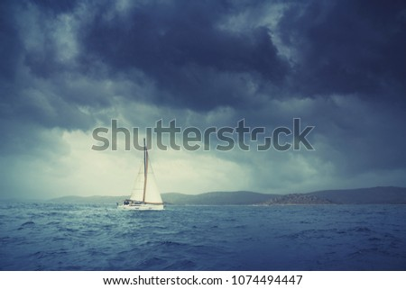 Boat sailing in the upcomming storm. Sailboat in bad weather sail at opened sea. Sailing yacht under heavy cloud sky.