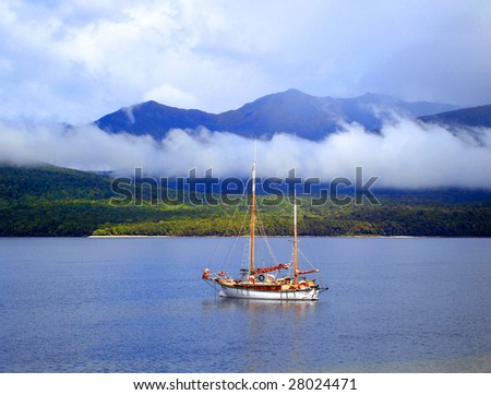 Boat sailing on Lake Te Anau, New Zealand, on a misty cold morning.