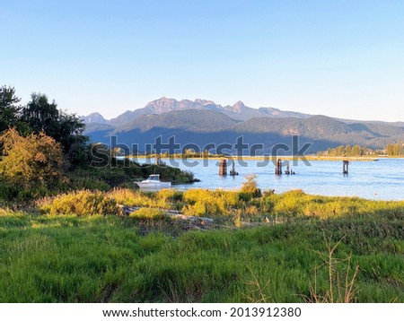 Boat sailing with view of Golden Ears Mountains from Traboulay PoCo Trail in Port Coquitlam, BC, Canada. July 24, 2021 Foto stock ©
