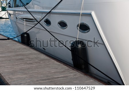 Boat secured to a wooden dock or pier with black fenders