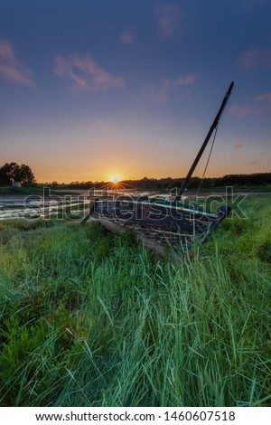 boat stranded in the grass at sunset