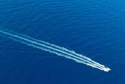 Boat surf foam aerial from prop wash in blue Majorca mediterranean sea