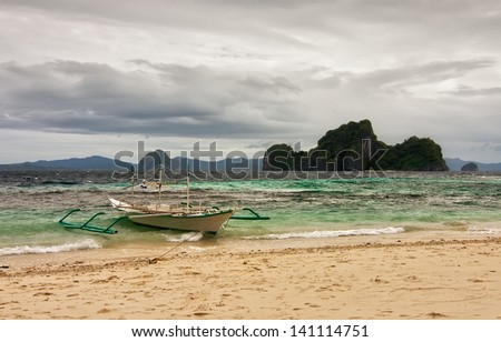 Boat tied to shore at stormy weather under heavy clouds with waving sea, El Nido, Palavan, Philippines