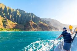 Boat tour with tourists along amazing Na Pali coast at sunset, Kauai island, Hawaii
