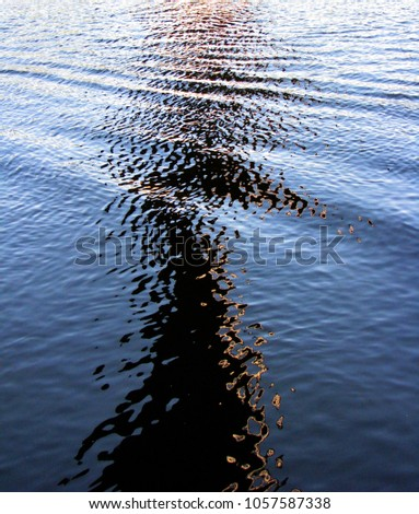 Boat track black giraffe neck and head silhouette illusion road reflection on wonderful deep blue summer water surface #1057587338