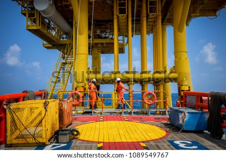 Boat transfer passenger during crew change in oil and gas industry platform.