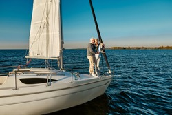 Boat trip. Happy senior man and woman hugging and enjoying amazing view while standing on the side of sail boat or yacht deck floating in the calm blue sea, sailing together