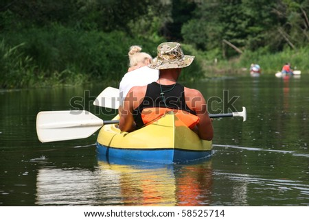boat trip: young couple kayaking on the river