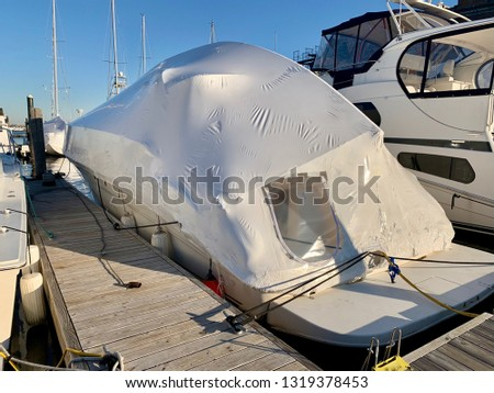 Boat waits for summer with shrink wrap cover