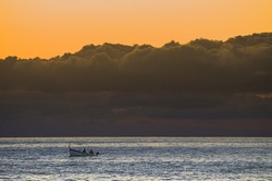 Boat with fishermen in the sea at sunset and clouds on the horizon