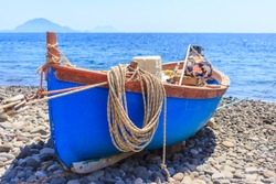 Boat, with hanging rope, docked on shore