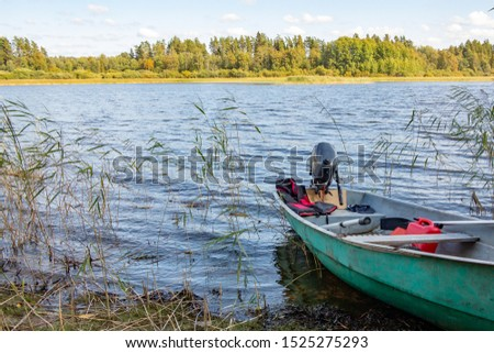 Boat with motor parked by the sandy bank of the river