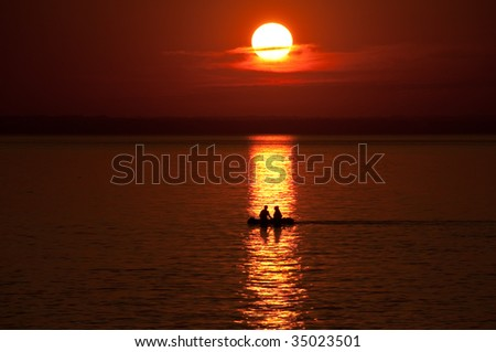 Boat with 2 people against an orange sunset