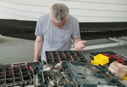 boat worker is looking for his corresponding tool.