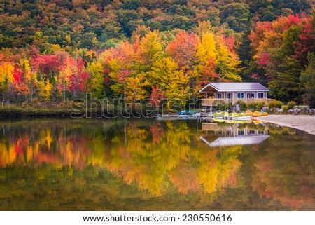 Boathouse and fall colors reflecting in Echo Lake, in Franconia Notch State Park, New Hampshire. #230550616