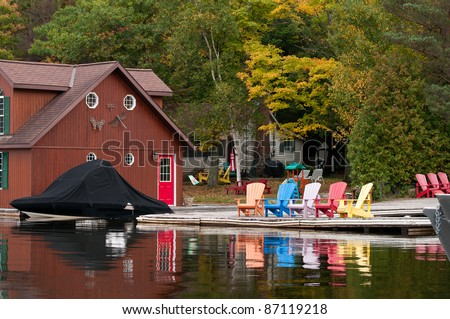 Boathouse with a boat and colorful chairs