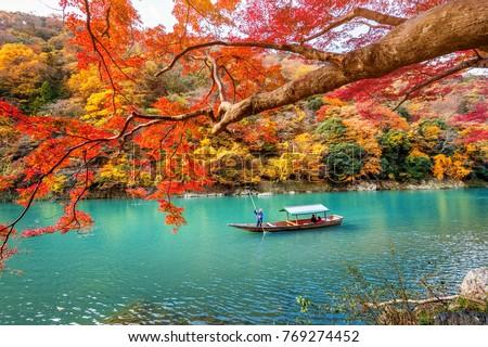 Boatman punting the boat at river. Arashiyama in autumn season along the river in Kyoto, Japan. #769274452