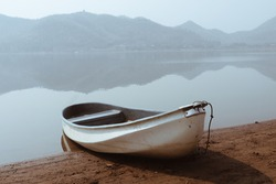 Boats and slip construction in lake with water in background of mountain in morning,Thailand.