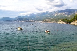 Boats and small boats anchored at sea. In the distance you can see the city of Budva and the hills above the city.