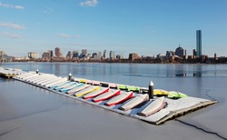boats at the MIT Sailing Pavilion on frozen Charles River overlooking Boston downtown in the background