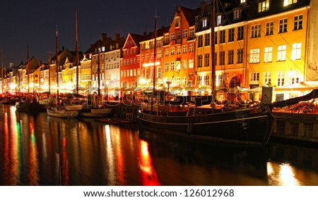 Boats at the Nyhavn harbor in night, Copenhagen, Denmark. Nyhavn is a famous 17th century embankment, canal and entertainment area in Copenhagen