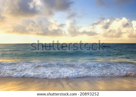 Boats bobbing in the ocean under the sunset of a Barbados beach.
