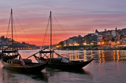 Boats carrying barrels of porto wine seen docking at river bank at sunset time at Porto, Portugal. The sky was burning red.