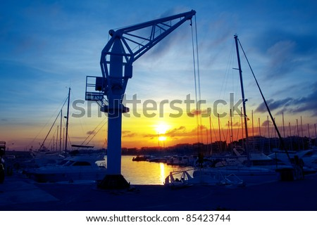 boats crane at sunset in marina port of Salou Tarragona Spain