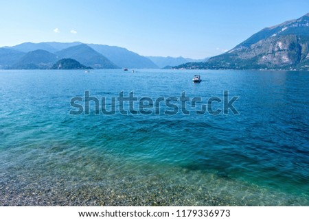 Boats cruising on azure water of Lake Como. View from shore. Mountains on background. Bellagio, Italy #1179336973