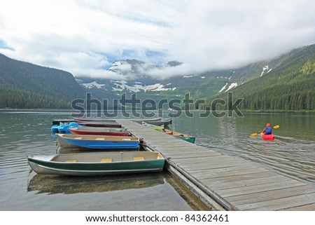 Boats Docked on Mountain Lake with Kayaker and Glacier in Background - Jasper National Park, Alberta, Canada