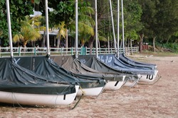 Boats in cover casing wrap on the beach.