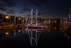 Boats in Lorient (France) harbour decorated for Christmas. The boats reflecting in the water. Evening.