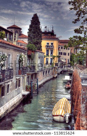 Boats moored down a street canal amongst gardens off the Grand Canal in Venice, Italy