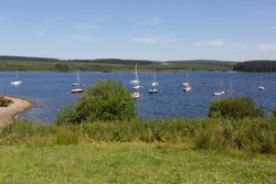 Boats moored on beautiful Llyn Brenig reservoir in North Wales, UK. Llyn Brenig is a reservoir located in North Wales, in the heart of the Denbigh Moors, at a height of 1200 feet.