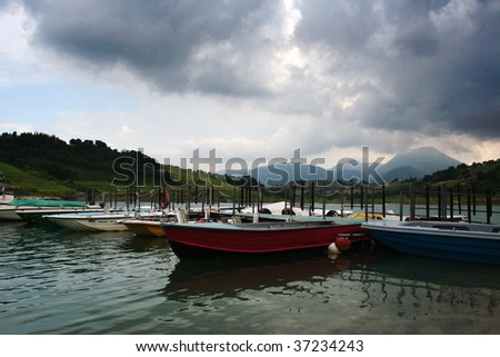 Boats on a lake with mountains in the background #37234243